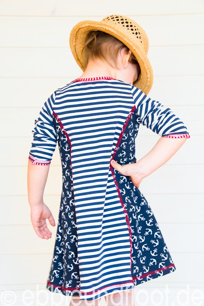 Lässige Pose in einem schicken sommerlichen, maritimen Kleid.