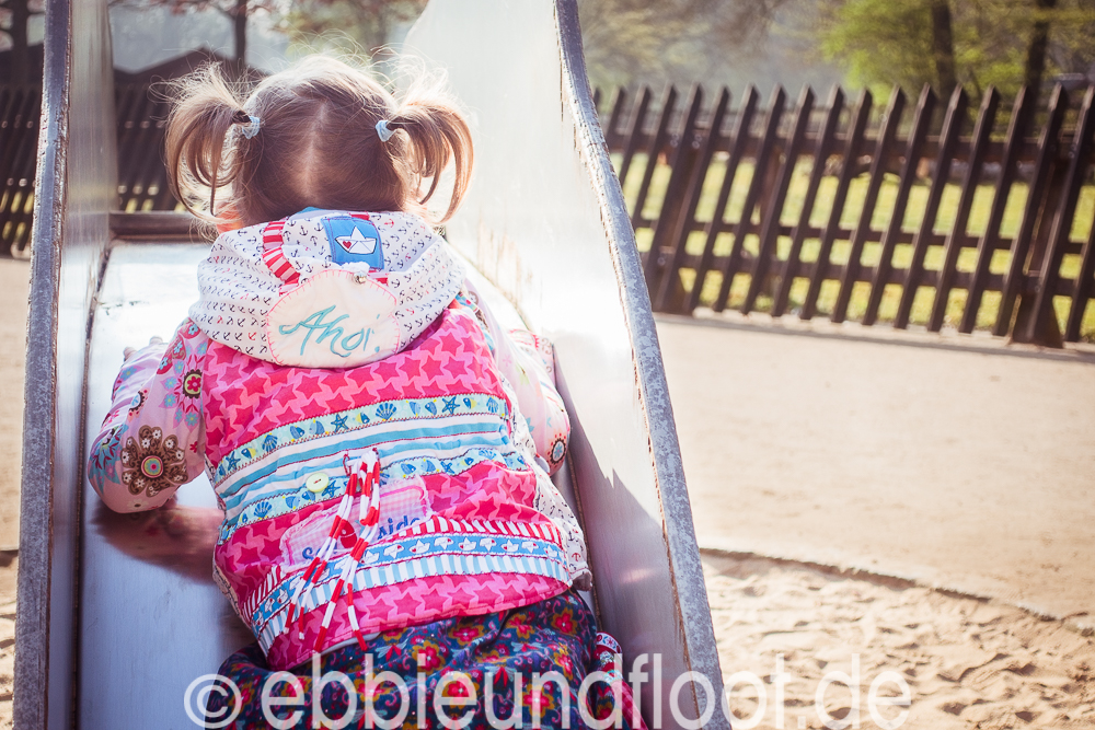 Kinder auf der Rutsche in maritimer Weste